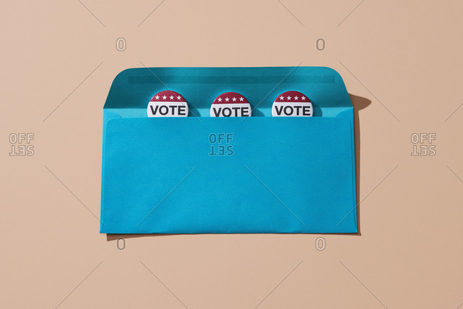 Vote badges in a blue envelope, on a salmon pink background