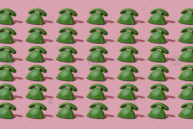 Mosaic of green telephones on a pink background
