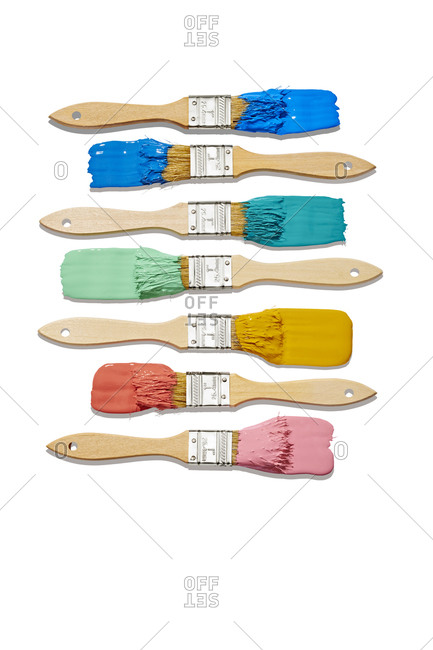Multiple Paintbrushes with Colorful Paint Organized on White Background