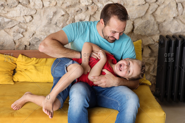 Playful father tickling laughing son on sofa at home