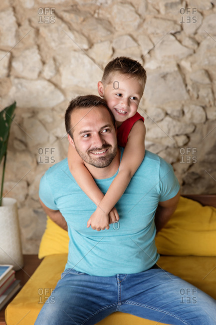 Smiling father sitting on sofa holding happy young boy on his back