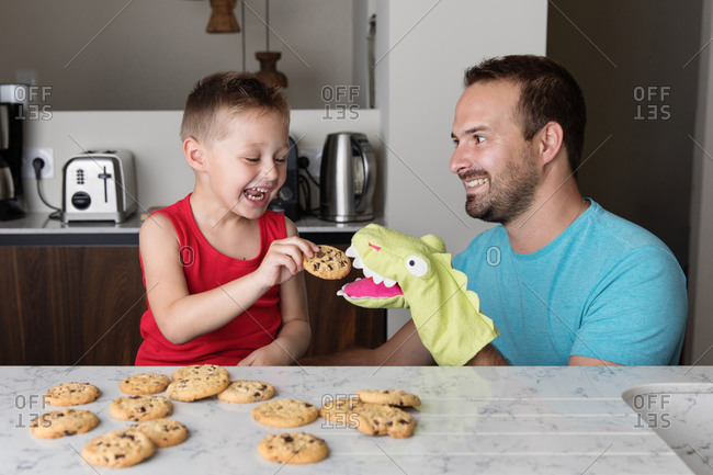 Happy father and son feeding glove puppet in kitchen while eating cookies
