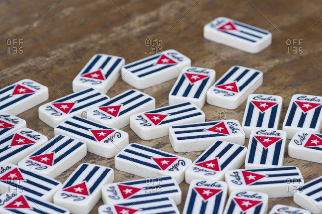 January 26, 2017: Cuba, Havana, pile of dominoes with Cuban flag on wood table.