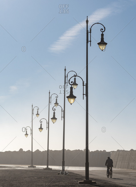 Africa, Morocco, Asilah. Man rides bike past lampposts.