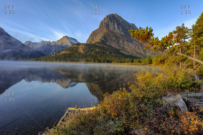 Grinnell Point and Mt. Gould reflection into Swiftcurrent Lake in early autumn in Glacier National Park, Montana, USA