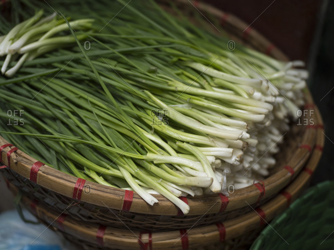 Vietnam, Hanoi, Old Quarter. Scallions in basket at market.