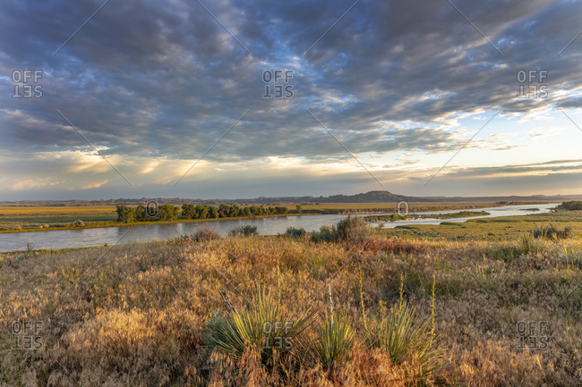 Sunrise and clouds over the Yellowstone River at the confluence with the Powder River near Terry, Montana, USA