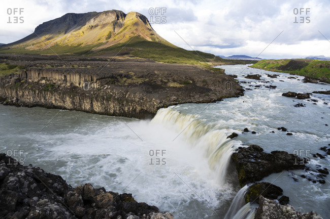 Iceland, Southern Highlands, Pjorsa River. The Pjorsa River flowing into the Pjofafoss waterfall with Mount Burfell in the background.