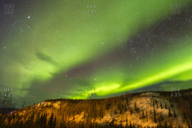 USA, Alaska, Fairbanks. Aurora borealis over mountain landscape.