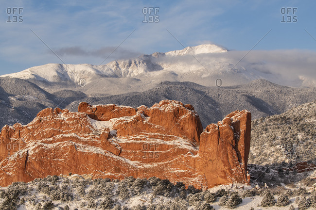 USA, Colorado, Garden of the Gods. Fresh snow on Pikes Peak and sandstone formation.