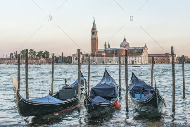 Italy, Venice. Gondolas on the waterfront with San Giorgio Maggiore Church in the background
