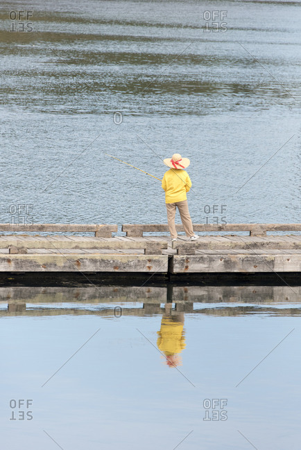 USA, Washington State, Whidbey Island. Deception Pass State Park dock. Woman fishing reflected in calm water