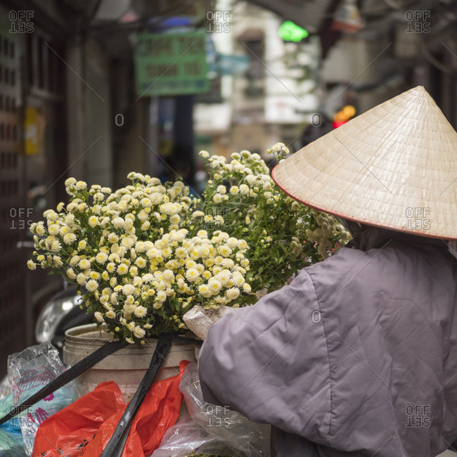 December 15, 2017: Vietnam, Hanoi. Old Quarter, Woman wearing conical Non La hat, selling flowers.