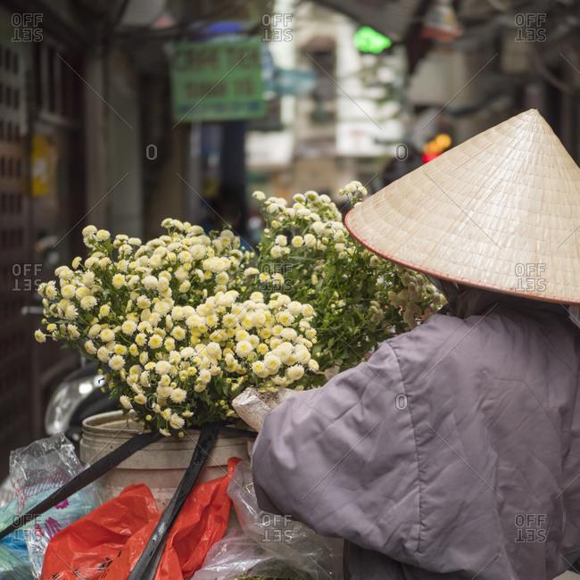 December 15, 2017: Vietnam, Hanoi. Old Quarter, Woman wearing conical Non La hat, selling flowers.