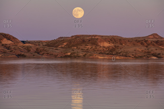 Full moonrise over Fort Peck Reservoir in the Charles M Russell National Wildlife Refuge near Fort Peck, Montana, USA