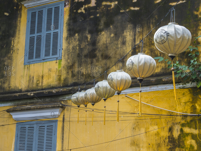 December 12, 2017: Vietnam, Hoi An. Old town historic district (UNESCO World Heritage Site). Electric lanterns hanging near an old yellow building.