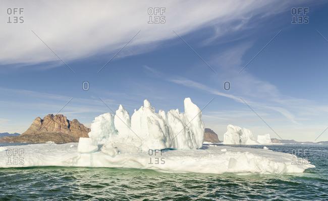 Iceberg in the Uummannaq Fjord System. Uummannaq Island in the background. Greenland, Denmark.