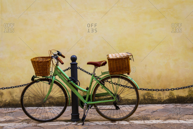Italy, Apulia, Province of Lecce, Lecce. Women's bicycle, with wicker baskets, propped against a post.