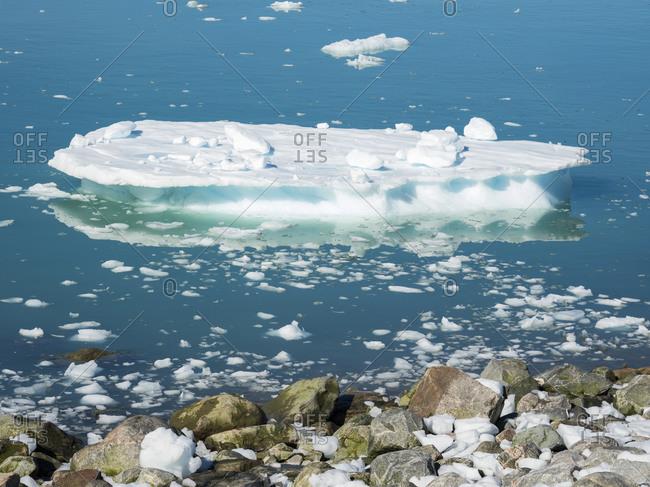 Fjord with iceberg on shore, near Eqip Glacier in Greenland, Danish Territory.