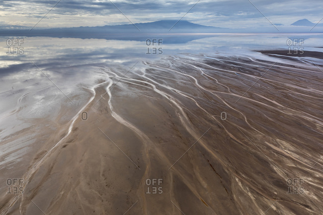 Africa, Tanzania, Aerial view of streams winding along shore of Lake Natron and distant Ol Doinyo Lengai volcano