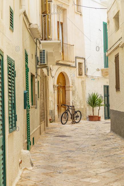 May 23, 2019: Italy, Apulia, Metropolitan City of Bari, Monopoli. Narrow street between buildings, with a bicycle.