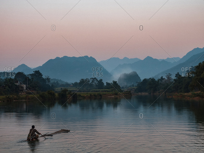 Asia, Vietnam, Pu Luong Nature Reserve. Lone man takes simple raft out onto river for sunset cruise.