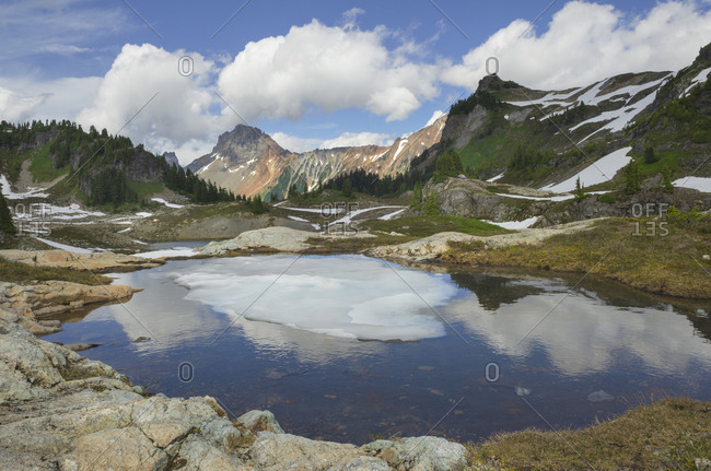 Partially thawed tarn, Yellow Aster Butte Basin. American Border Peak is in the distance. Mount Baker Wilderness, North Cascades, Washington State