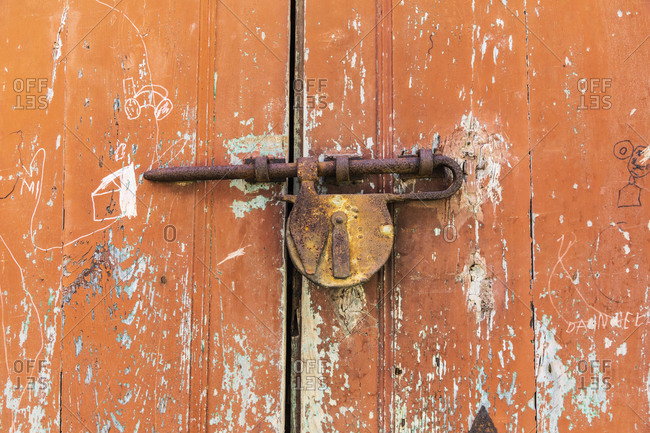 April 16, 2019: Italy, Sicily, Province of Messina, Novara di Sicilia. Rusted lock on an old door in the medieval hill town of Novara di Sicilia.