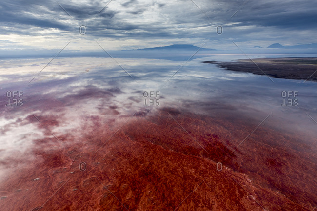 Africa, Tanzania, Enhanced contrast aerial view of patterns of red algae and salt formations in shallow salt waters of Lake Natron and distant Ol Doinyo Lengai volcano
