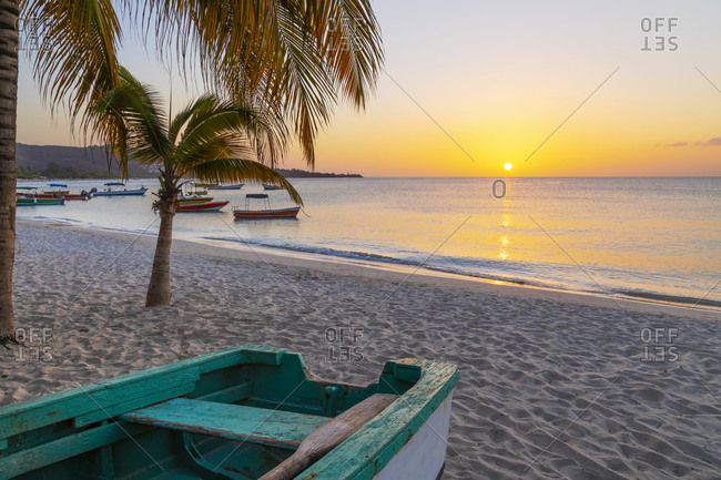 Caribbean, Grenada, Grenadines. Sunset and wooden fishing boat on Grand Anse Beach.