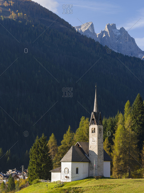 The church, in the background Focobon mountain range in the Pale di San Martino. Caviola, part of Falcade alto in Val Biois, Italy.
