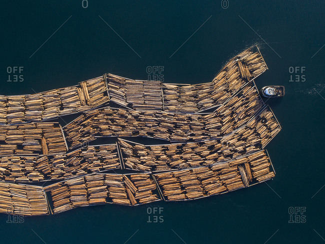 Canada, British Columbia, Campbell River, Aerial view of tugboats towing boom of freshly cut logs toward Seymour Narrows along Vancouver Island on summer evening