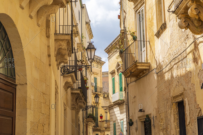 Italy, Apulia, Province of Lecce, Lecce. Stone buildings and iron balconies along a narrow street.