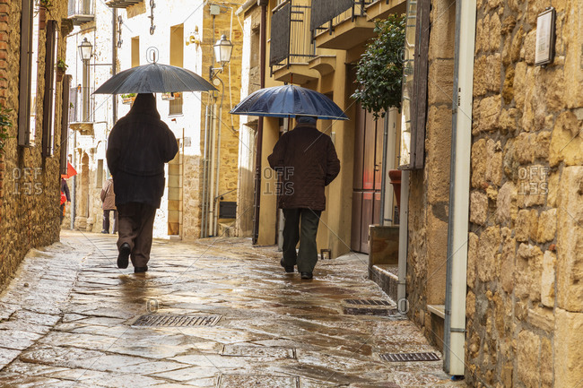 April 12, 2019: Italy, Sicily, Palermo Province, Gangi. April 12, 2019. Two men walking in the rain with umbrellas on a cobblestone street in Gangi