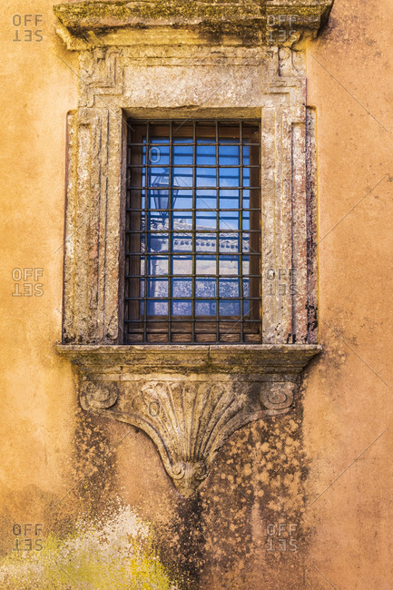 Italy, Sicily, Trapani Province, Erice. Barred window with a decorative stone frame on a building in the ancient hill town of Erice.
