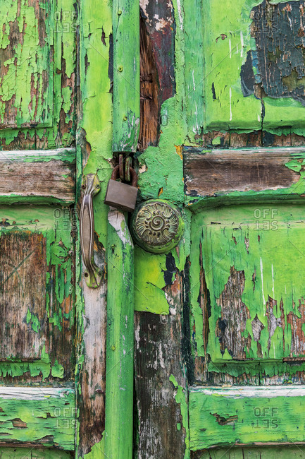 Italy, Basilicata, Province of Matera, Matera. Old weathered green door with peeling paint.