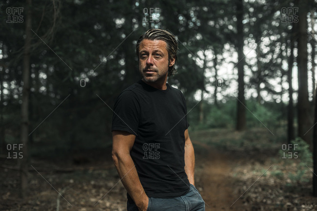 Man walking alone in the woods looking away with his hands in his pockets