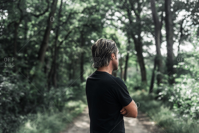 Rear view of man in the woods looking away with his arms crossed