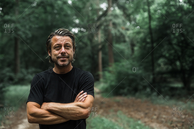 Portrait of a man standing alone in the woods looking away with his arms crossed