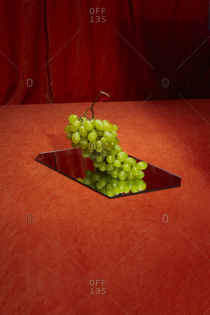 Green grapes reflecting in mirror on red background