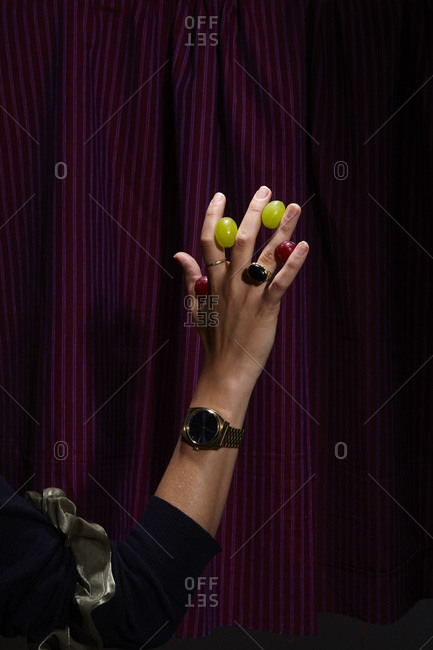 Woman's hand with grapes in between her fingers