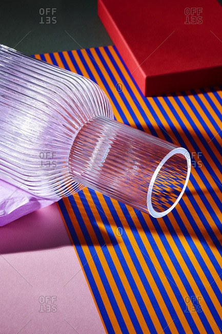 Glass vase lying on colorful striped paper
