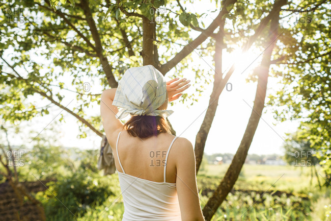 Rear view of woman blocking sun from her eyes