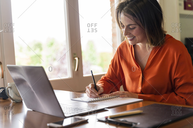 Smiling businesswoman writing in notepad while working at home