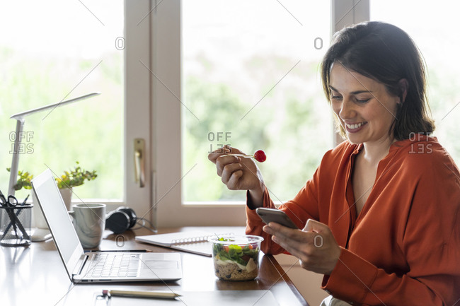 Smiling business person using mobile phone while eating salad at home