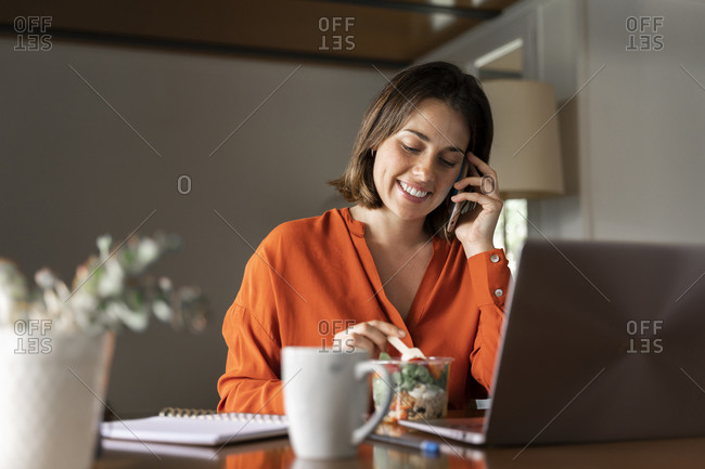 Smiling businesswoman talking on smart phone while eating salad at home