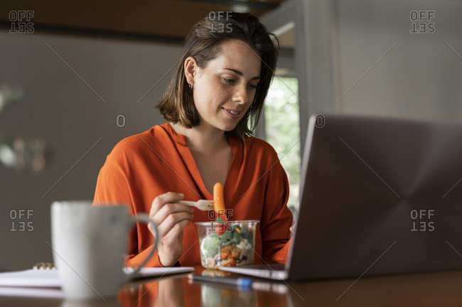 Smiling entrepreneur eating salad at home