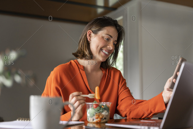 Smiling entrepreneur using mobile phone while eating salad at home