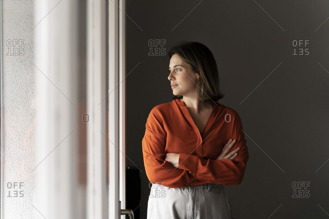 Businesswoman with arms crossed looking through window at home