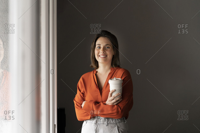 Portrait of smiling businesswoman with coffee cup at home